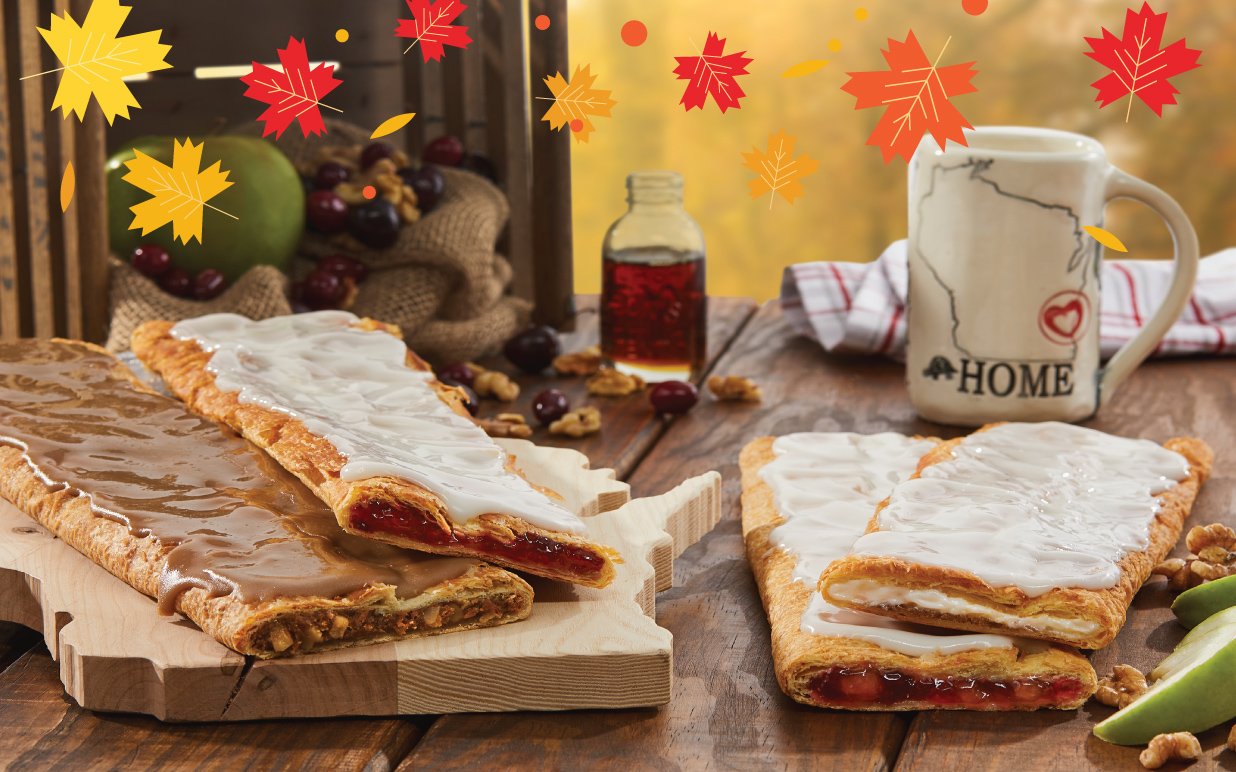 Four stick sized Kringle on a Wisconsin shaped board surrounded by maple, syrup, fruits, nut and coffee mug.