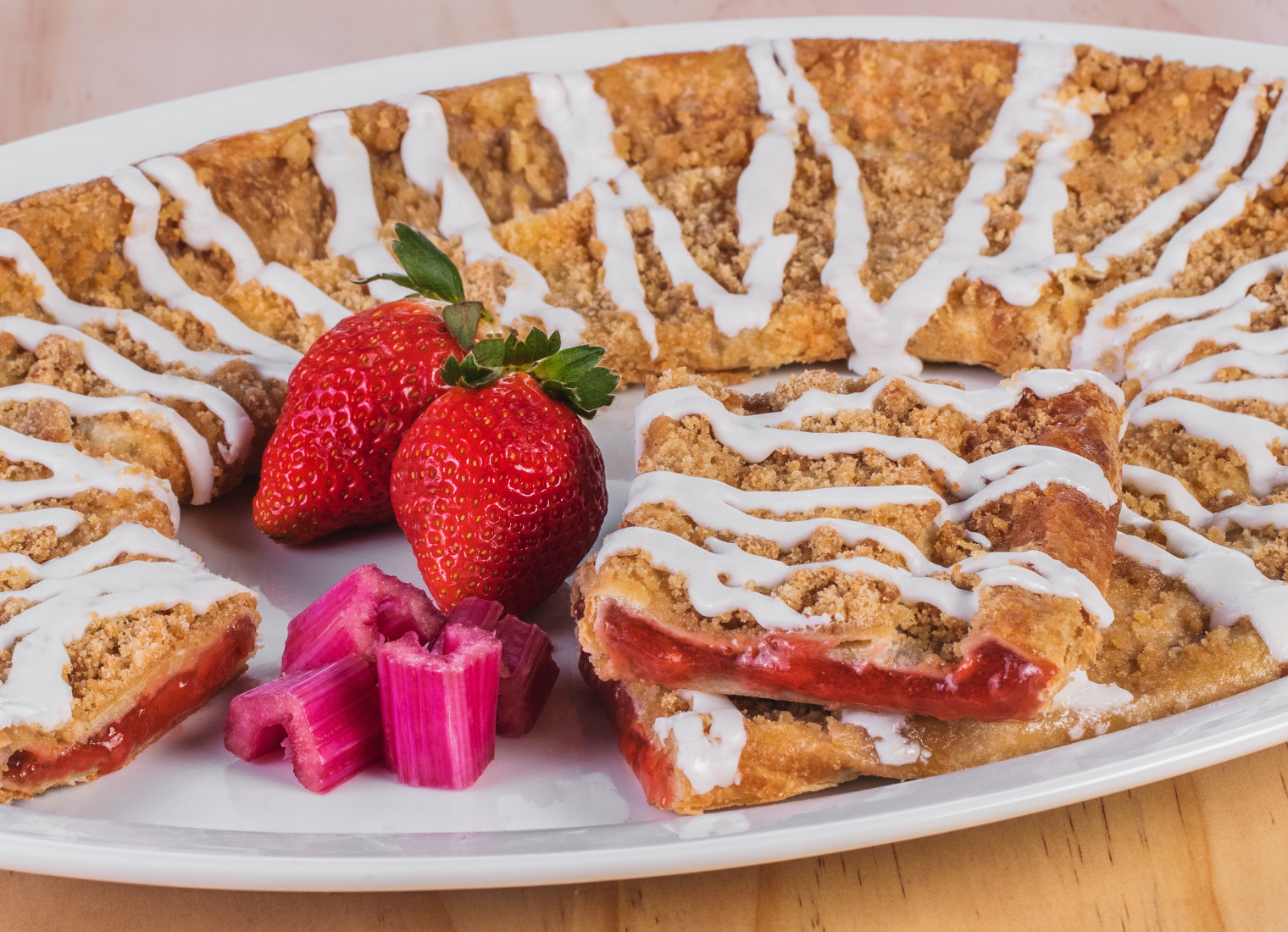 Strawberry Rhubarb Kringle on a plate with a slice cut out along with pieces of rhubarb to the side