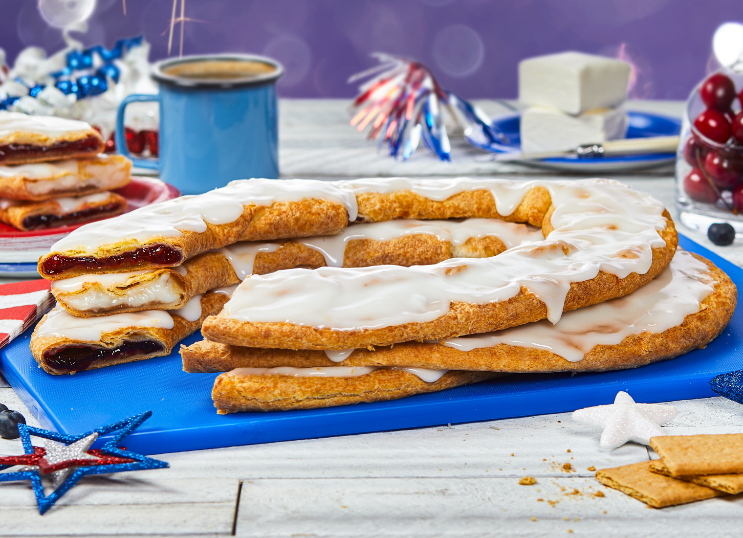 Three Kringle stacked on blue platter surrounded by red, white and blue decorations