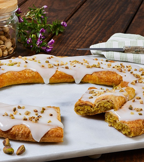 Pistachio Kringle on a dark wood table with a green tea towel and a jar of pistachios.