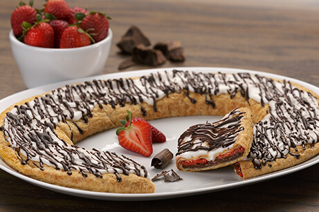 Chocolate Strawberry Kringle on a white plate surrounded by a bowl of strawberries and chucks of chocolate.