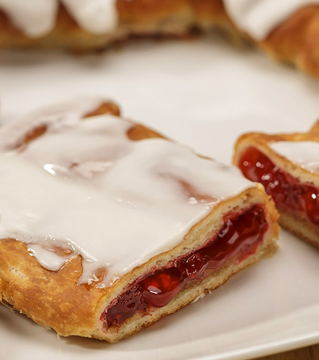 Cranberry Kringle on white plate with a scattering of cranberries.