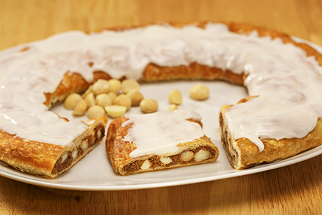 Macadamia Nut Kringle on white plate with scattering of walnuts.