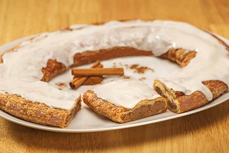 Cinnamon Kringle on white plate with cinnamon sticks.