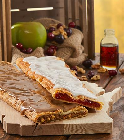Four stick Kringle surrounded with apples, nuts and cranberries in a wooded crate along with Wisconsin mug.