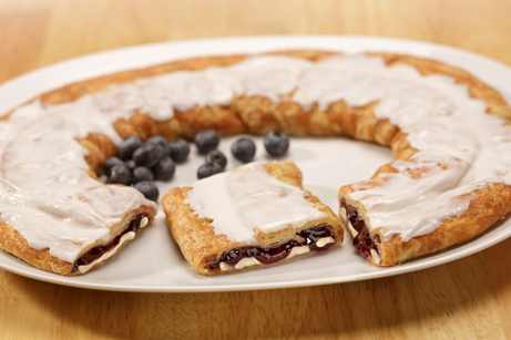 Blueberry Cheesecake Kringle on a white plate surrounded by blueberries.