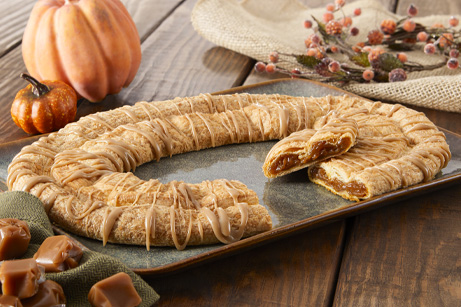 Pumpkin Caramel Kringle on a grey plate with pumpkins and cubed caramels on the side.