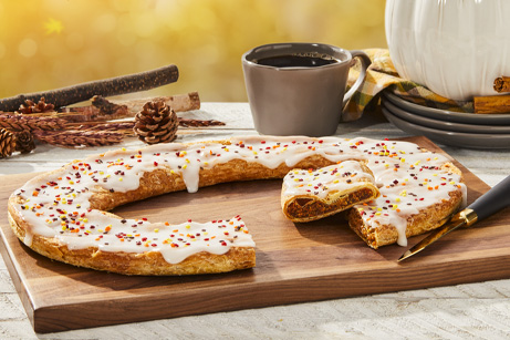 Autumn Kringle on wood board with coffee mug, pine cones, stacked plates and white pumpkin.