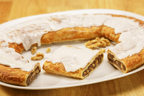 Walnut Kringle on white plate with scattering of walnuts.