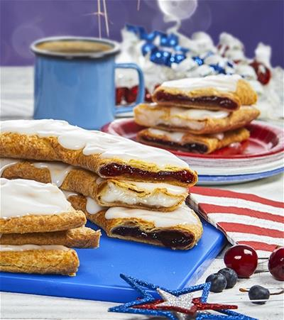 Three slices of kringle layered on top of one another on a plate surrounded by red, white, and blue decorations