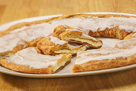 Cheesecake Kringle on white plate with slices cut out.