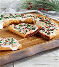 Santa's Cinnaberry Kringle on wood board with bowl of cranberries, cinnamon sticks and festive pine branch.