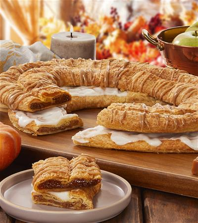 Pumpkin Caramel and Apple Cinnamon Kringle with slices cut out on separate plate surrounded by pumpkin, caramel cubes, apples and fall decorations.