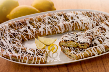 Lemon poppyseed kringle with a drizzle of icing with a close up shot and a wide angle view of the kringle on a platter