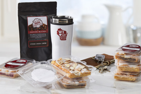 Single-served sized Kringle in packaging with coffee bag, travel mug, keys and wallet.