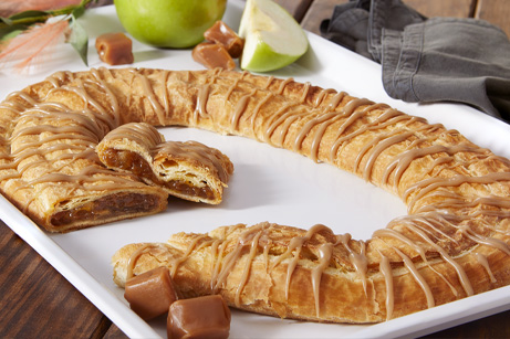 Caramel Apple Kringle on white tray surrounded by sliced apple, cubed caramel pieces and grey napkin.
