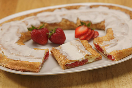 Strawberry Cheesecake Kringle on a white plate with slices strawberries.