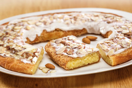 Almond Kringle sitting on a white plate with a few almonds next to the Kringle.