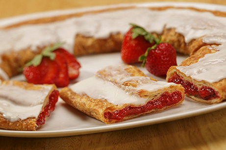 Strawberry Kringle on a white plate with sliced and whole strawberries.