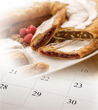 Pecan and Raspberry Kringle with a calendar in the background.