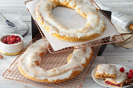 Raspberry and Pecan Kringle on baking trays with scattering raspberries and pecans with a rolling pin.