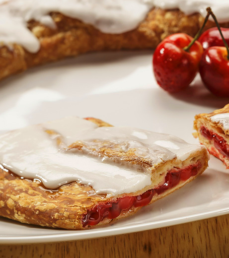 Cherry Kringle on white plate with a few cherries.