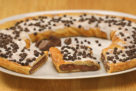 Chocolate Chip Kringle on white plate with chunks of chocolate.