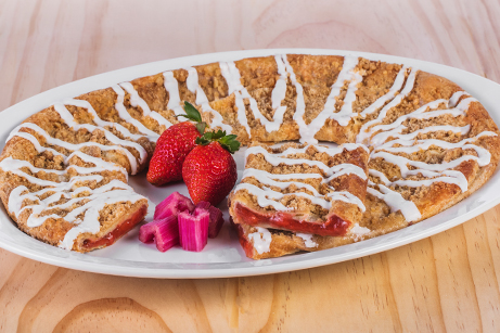 Strawberry Cheesecake Kringle on a white plate with sliced strawberries and rhubarb.