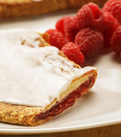 Raspberry Kringle on a white plate with a few raspberries.