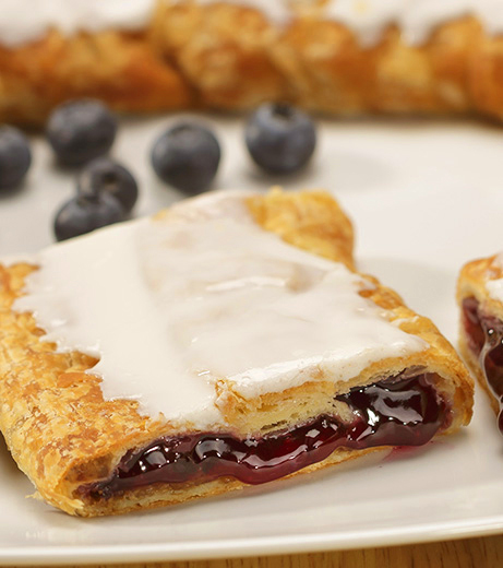 Blueberry Kringle on white plate with scattered blueberries.