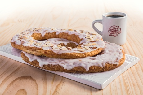 Two Kringle on a white platter with a mug of coffee