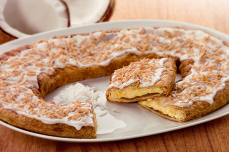 Coconut Kringle of a white plate with coconut shavings and coconut halves.