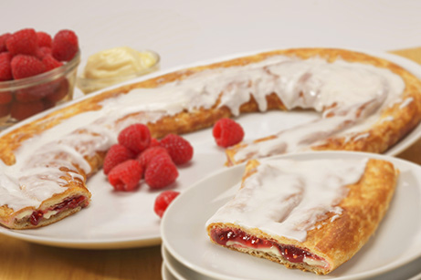 Raspberry Cheesecake Kringle on white plate, slice on smaller plate surrounded by raspberries.