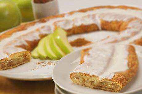 Apple Cinnamon Kringle on white plate with sliced apples and cinnamon on the side.